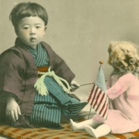 1071. [Child with doll and American and Japanese flags]