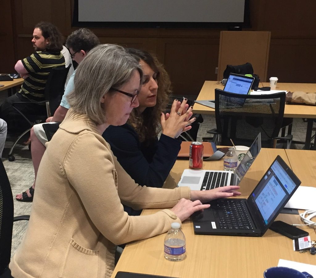 Image of a faculty member and librarian working on their laptops.